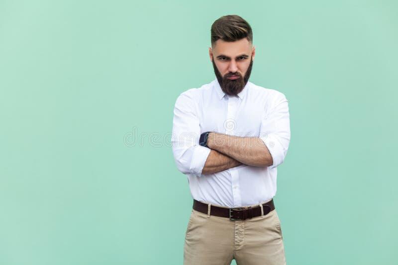Förbittrad man, med armar vikta, över ljus - grön bakgrund i studioskott royaltyfria foton
