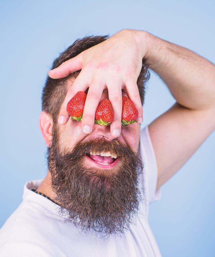 Förblinda av jordgubben Mannen uppsökte hipsterhållhanden med jordgubbar som var främsta av ögon Jordgubbe på min mening Mannen k arkivfoto