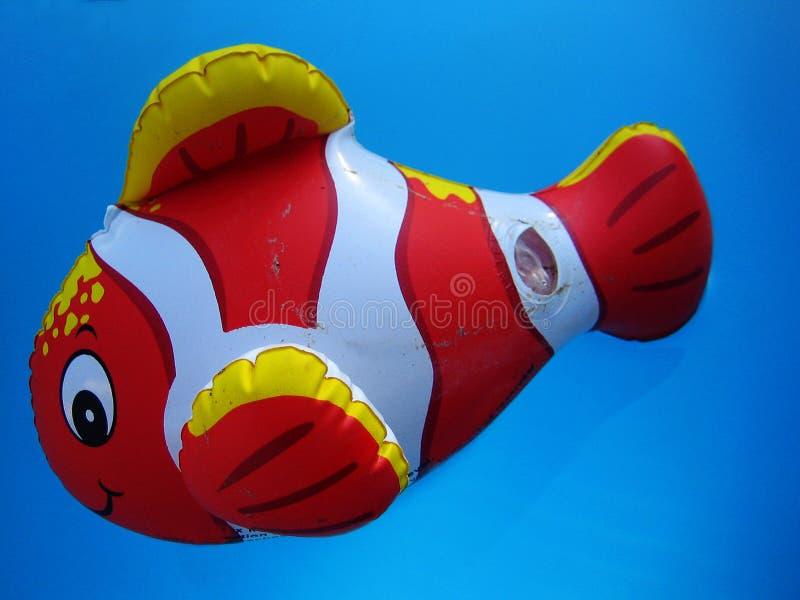 Förbluffa clownfiskleksaken i djupblå tapet för pölvattenmakro royaltyfri bild