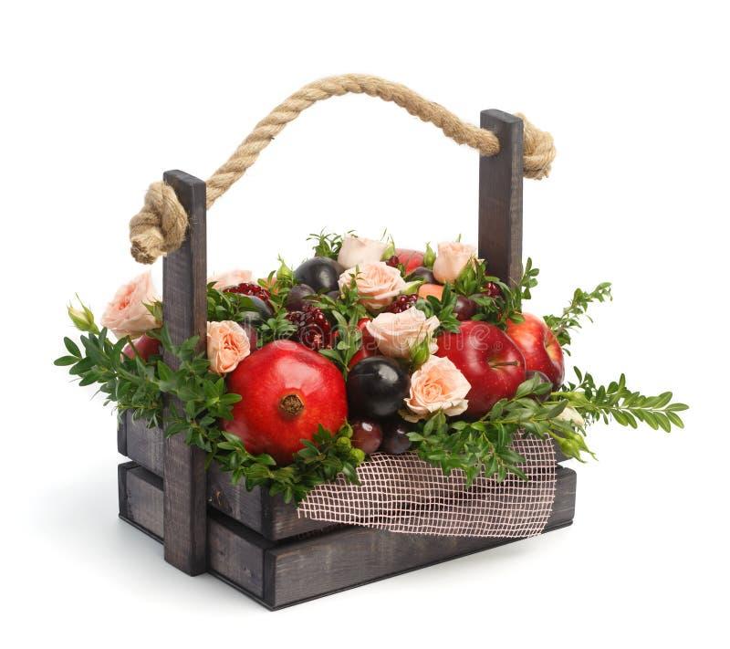Förbluffa den ätliga årsdaggåvan i form av en träask som fylls med rosor och olika frukter på en vit bakgrund royaltyfria foton