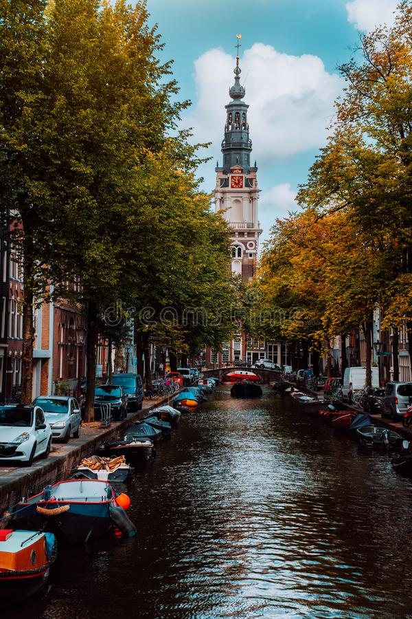 Förbluffa den Groenburgwal kanalen i Amsterdam med den Soutern kyrkan Zuiderkerk på solnedgången i höst royaltyfria foton