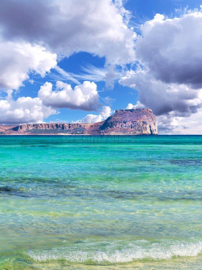 F?rbluffa den tropiska stranden, det klara bl?a lugna havet, ?n i bakgrunden och h?rlig himmel royaltyfria foton