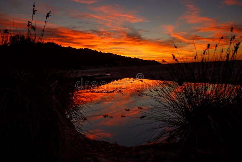 Förbluffa flamma solnedgånglandskap över ön och himlen ovanför den med en enorm sol Solnedgångsikt på stranden arkivbilder