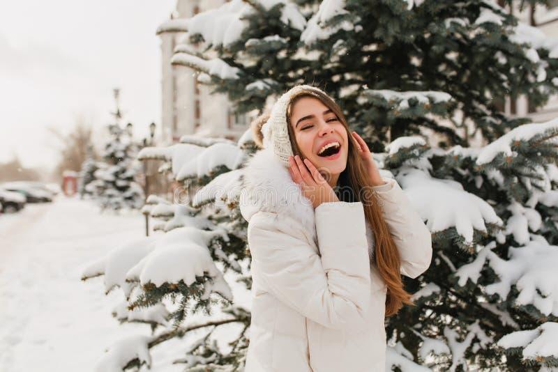 Förbluffa flickan i vit kläder som har gyckel i vinterdagen som poserar för foto Utomhus- stående av den nöjda caucasian kvinnan royaltyfri foto