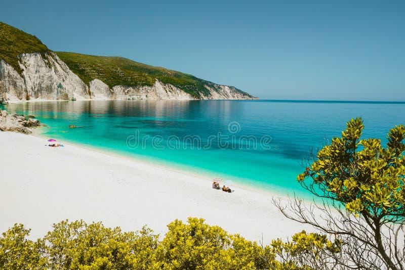 Förbluffa Fteri sätta på land lagun, Cephalonia Kefalonia, Grekland Turister under paraplyet kopplar av nära klar blå smaragdturq arkivfoto