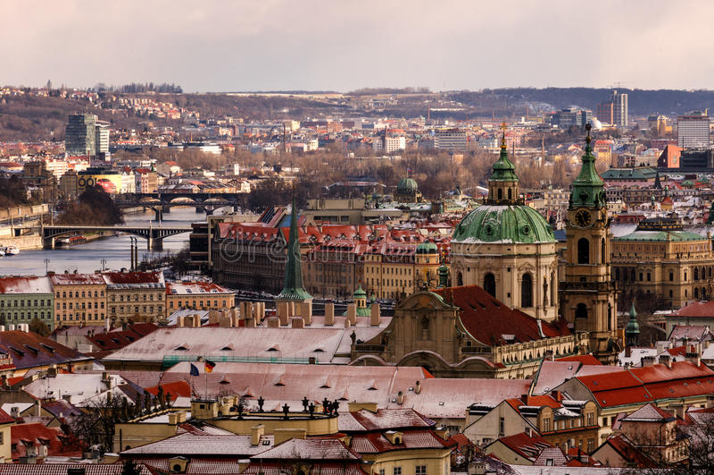 Förbluffa kyrkan för St Nicolas under vinterdag efter storm för tung snö med snöräkningen på tak Prague tjeckisk republik royaltyfria foton