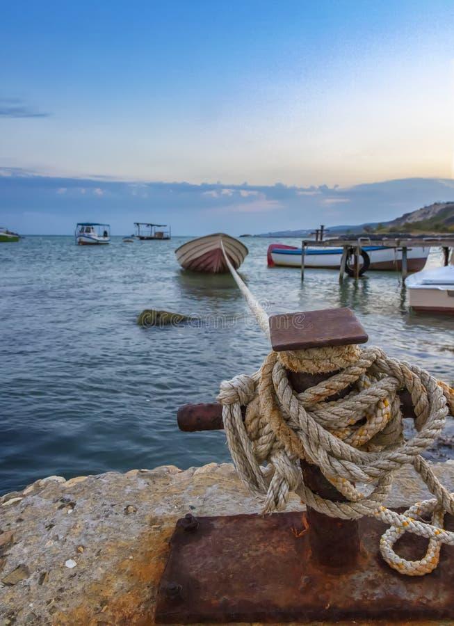 Förbluffa länge ett rep som ankrar fiskebåten på pir arkivbilder