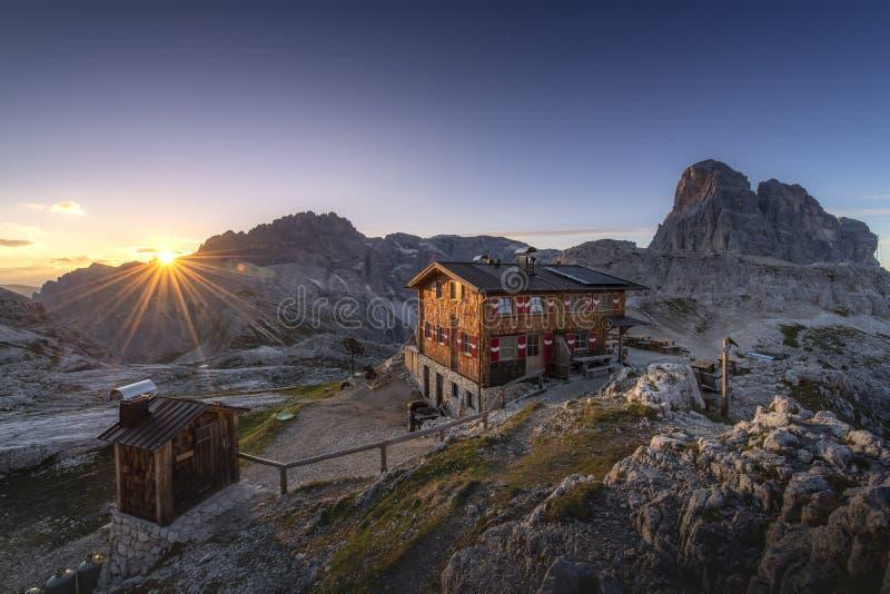 Förbluffa landskapsikt av kojan och berget på soluppgångmorgonbakgrund från Dolomites, Italien arkivbild