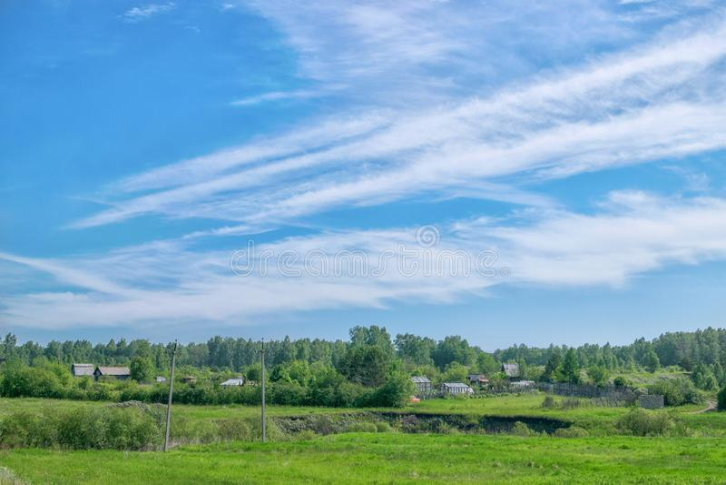 Förbluffa moln över byn och skogen arkivbild
