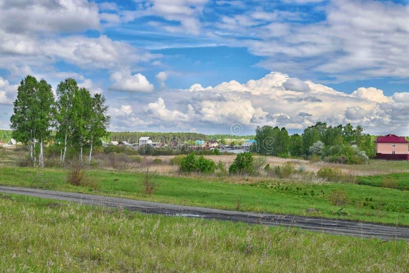 Förbluffa moln över by på sommar nära skog fotografering för bildbyråer