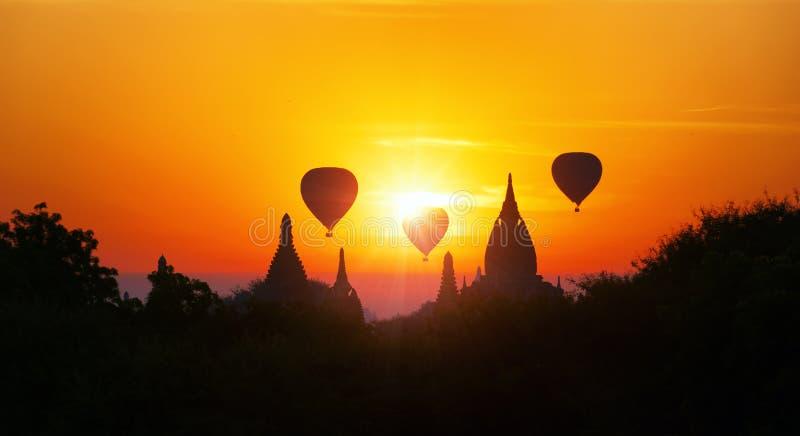 Förbluffa Myanmar solnedgångpanorama med tempel och luftballonger royaltyfri bild