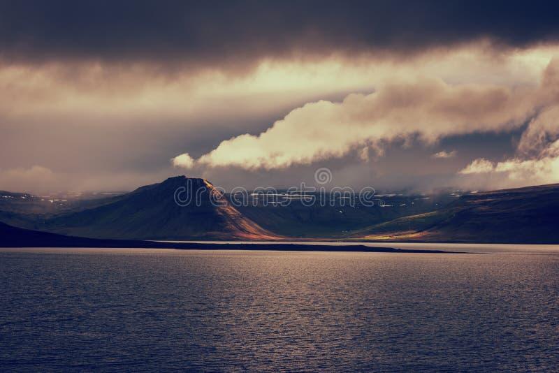 Förbluffa naturen, sceniskt landskap för natt i månsken med vatten, vulkaniska berg och molnig himmel, Island Utomhus- lopp arkivbilder