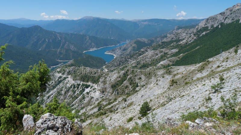 Förbluffa naturlandskap i en nationalpark med en sjö och gröna gråa berg för skog och för öken Blå flod och kanjon Mavrovo royaltyfri fotografi