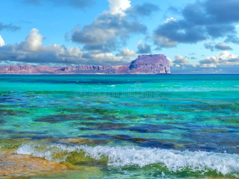 F?rbluffa sikten av den Gramvousa ?n fr?n den Balos stranden - v?ndkretsparadis, kristallklart turkosvatten arkivbilder