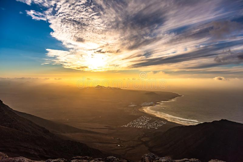 Förbluffa solnedgång över för Famara Lanzarote för havsemesterortstrand öar kanariefågel, Spanien royaltyfri bild