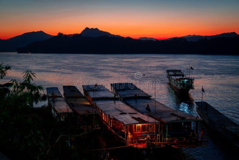 Förbluffa solnedgång i luangprabang över Mekonget River Turist och husfartyg i vattnet Himmel är på brand arkivbild