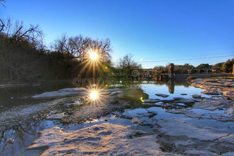 Förbluffa solnedgånglandskap på buskig liten vik i Round Rock, Texas Solen och stenar reflekteras i vatten med blå himmel arkivbild