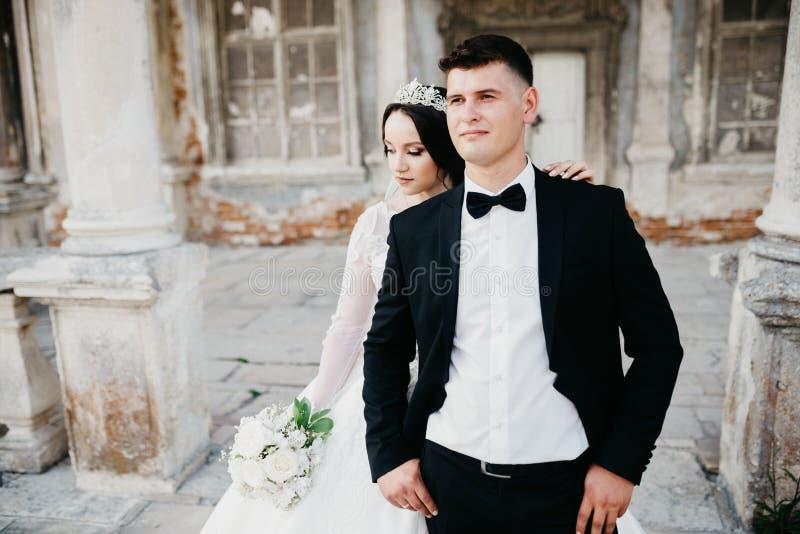 Förbluffa ståenden av ett gifta sig par nära den gamla slotten arkivfoto