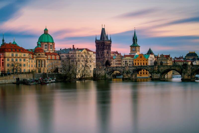 Förbluffa torn av den Charles bron med reflexion på den Vltava floden under molnig solnedgång, Prague, Tjeckien royaltyfri bild