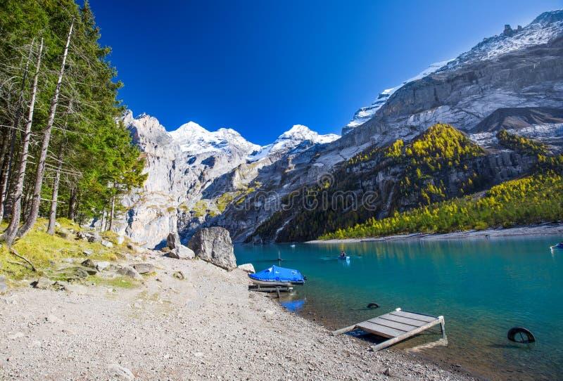 Förbluffa tourquise Oeschinnensee med vattenfall och schweiziska fjällängar, Berner Oberland, Schweiz royaltyfria foton