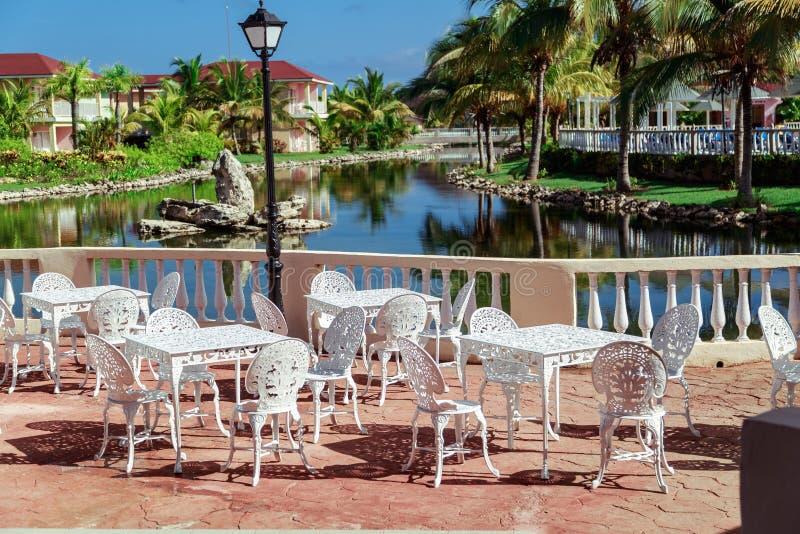 Förbluffa ursnygg inviterande sikt av minnessemesterortlandskapet, utomhus- kafé, uteplats med stolar för klassiker för metalltap arkivfoto