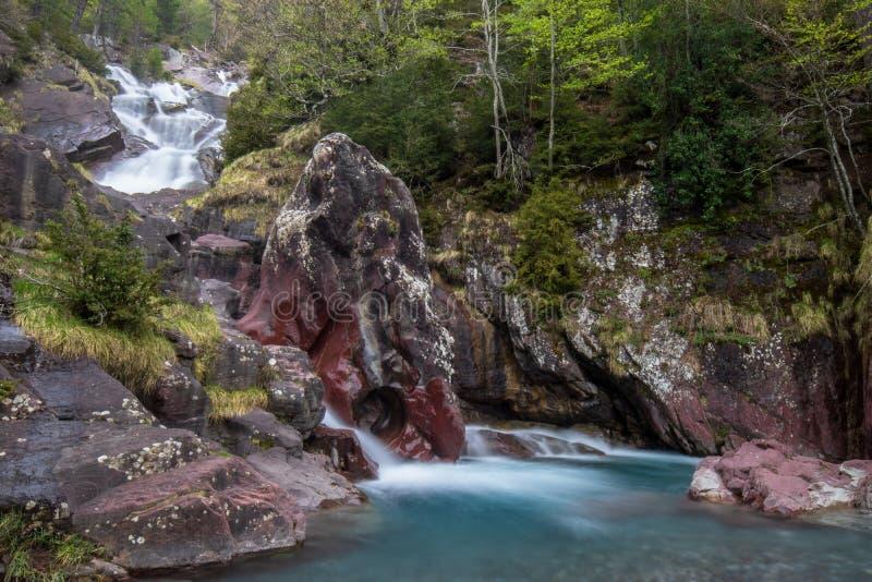 Förbluffa vattenfallet till och med stenarna fotografering för bildbyråer