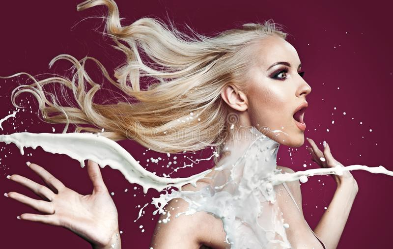 Förbluffad blond dam som hälls med vit målarfärg arkivfoton