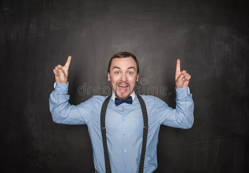 Förbluffade affärsmannen eller läraren som har idé och, fingrar upp på svart tavla royaltyfri fotografi