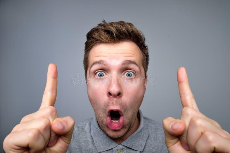 Förbluffat och förvånat peka för ung stilig man upp med fingrar fotografering för bildbyråer