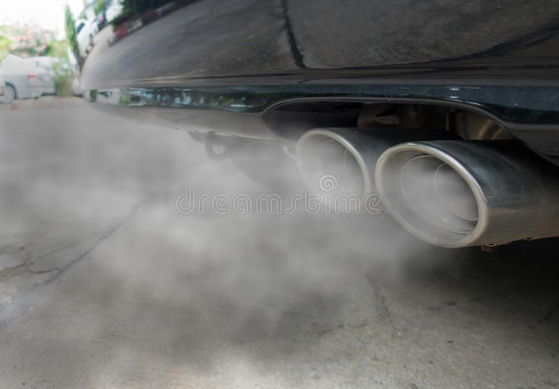 Förbränning ångar att komma ut ur det svarta bilavgasrörröret, luftföroreningbegrepp arkivbild