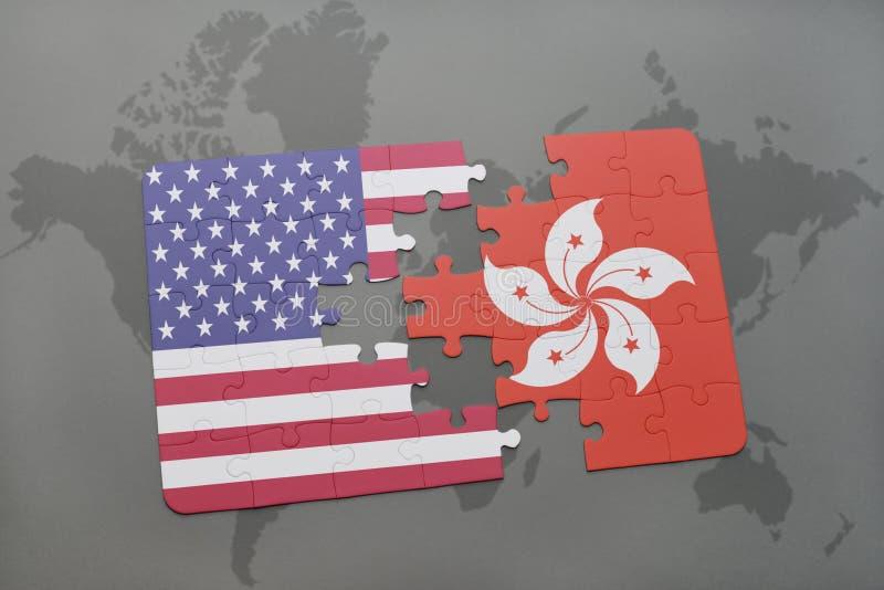 Förbrylla med nationsflaggan av USA och Hong Kong på en världskartabakgrund royaltyfri fotografi