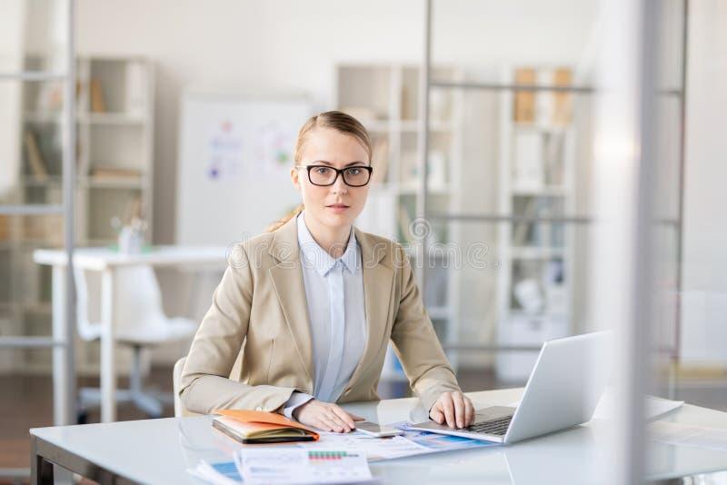 Förbryllad affärskvinna som gör skrivbordsarbete arkivbild