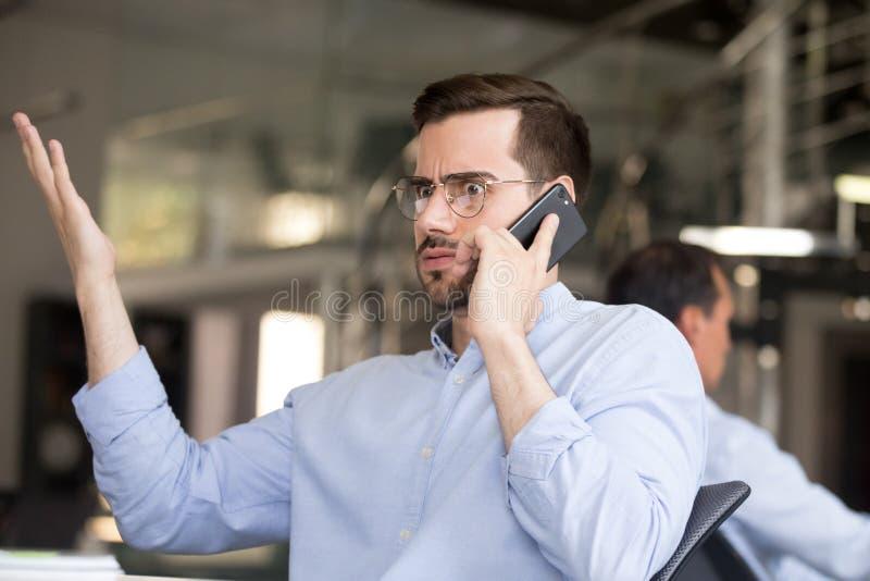 Förbryllad affärsman som i regeringsställning talar på telefonen royaltyfri foto