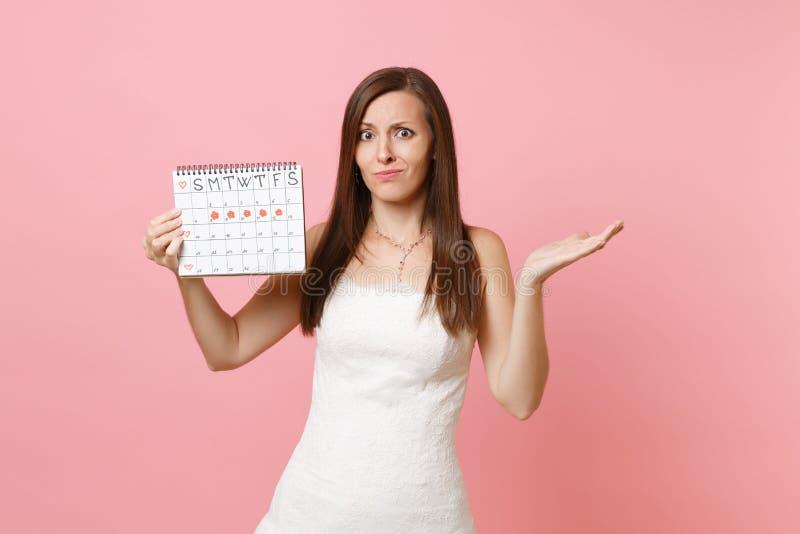 Förbryllad skyldig brudkvinna i kalendern för perioder för håll för bröllopsklänningspridninghand den kvinnliga för att kontrolle arkivfoto