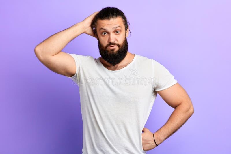 Förbryllad stilig man som skrapar hans huvud i bryderi arkivfoto