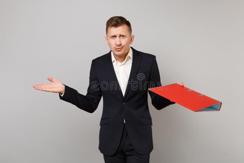 Förbryllad ung affärsman i den klassiska svarta dräkten, fördelande händer för skjorta med den röda mappen för legitimationshandl royaltyfri foto