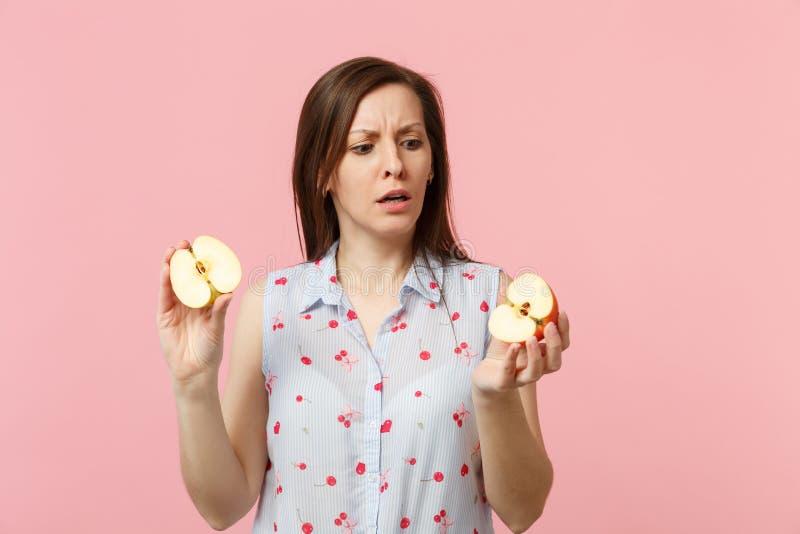 Förbryllad ung kvinna i sommarkläder som rymmer i handhalfs av ny mogen äpplefrukt som isoleras på rosa pastell arkivfoton