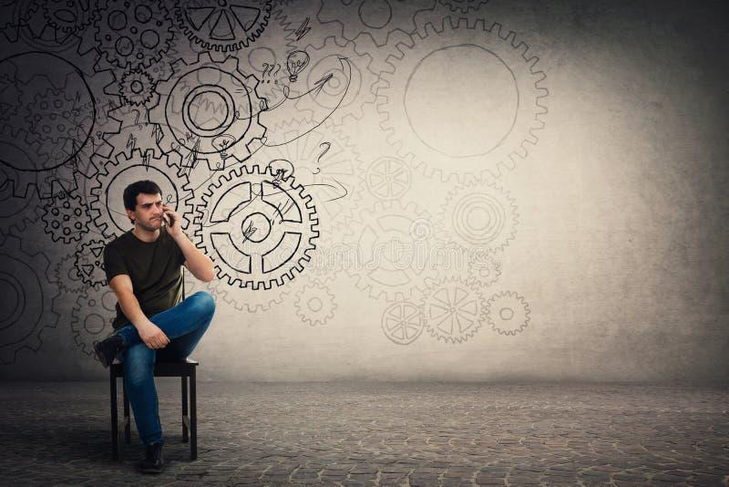 Förbryllad ung man som sitter på stol som talar på hans smartphone, tänkande hårt allvarlig grabb med kugghjulkugghjulhjärnan arkivfoto