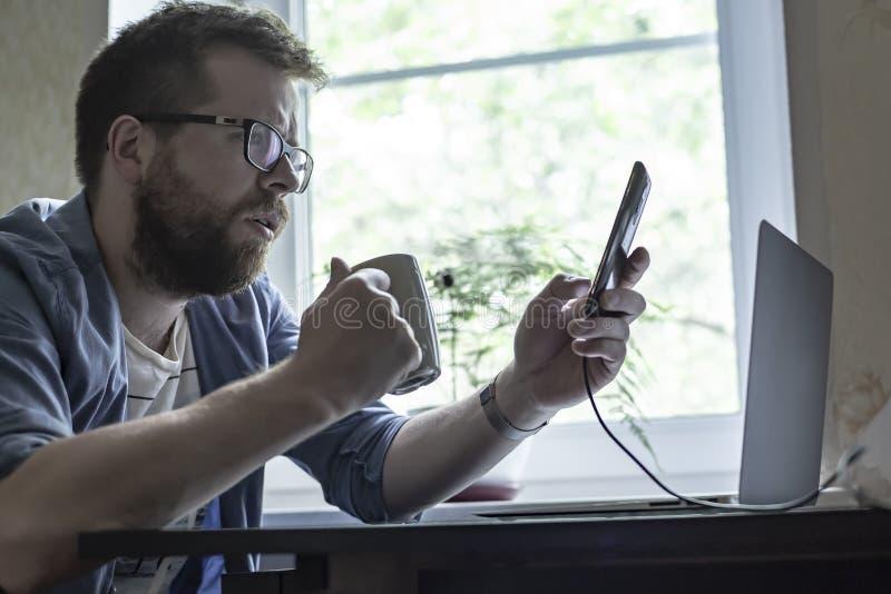 Förbryllat av en skäggig man i exponeringsglas rymmer i hans händer en smartphone, och en kopp av den varma drinken på tabellen ä arkivbild