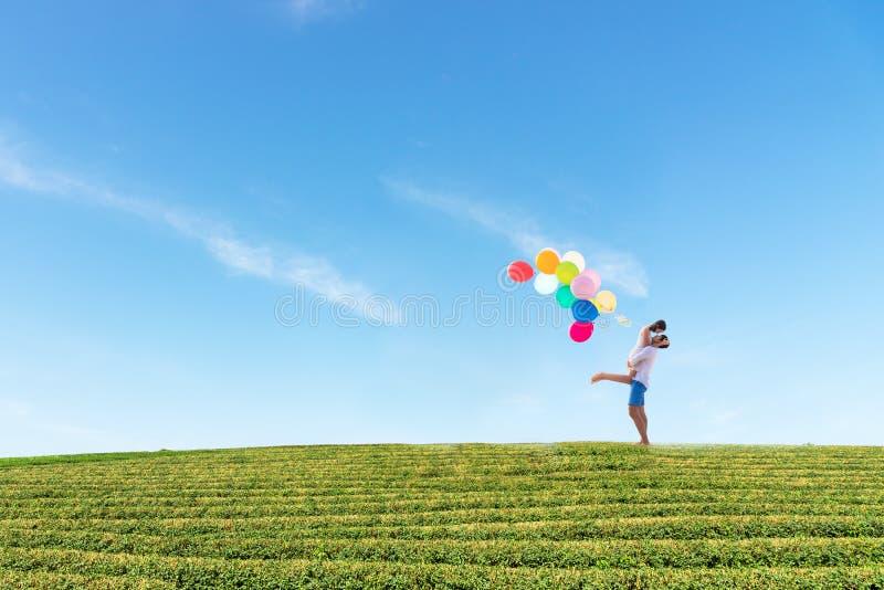 förbunden förälskelse Att le den asiatiska unga mannen är den hållande flickvännen i hans armar med den mång- färgballongen som ä arkivfoto