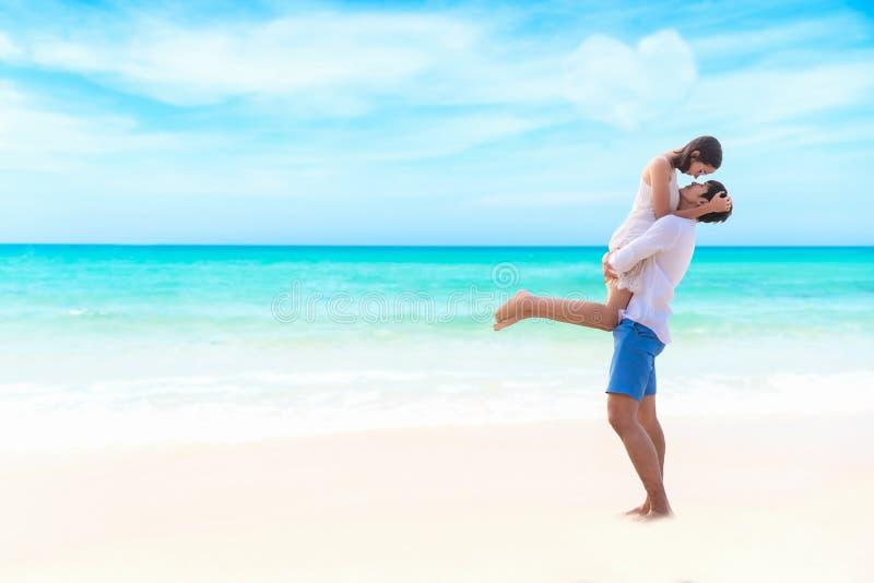 förbunden förälskelse Att le den asiatiska unga mannen är den hållande flickvännen i hans armar på stranden på aftontid, för hjär arkivfoton