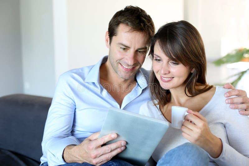 Förbunden hemma genom att använda tableten royaltyfri fotografi