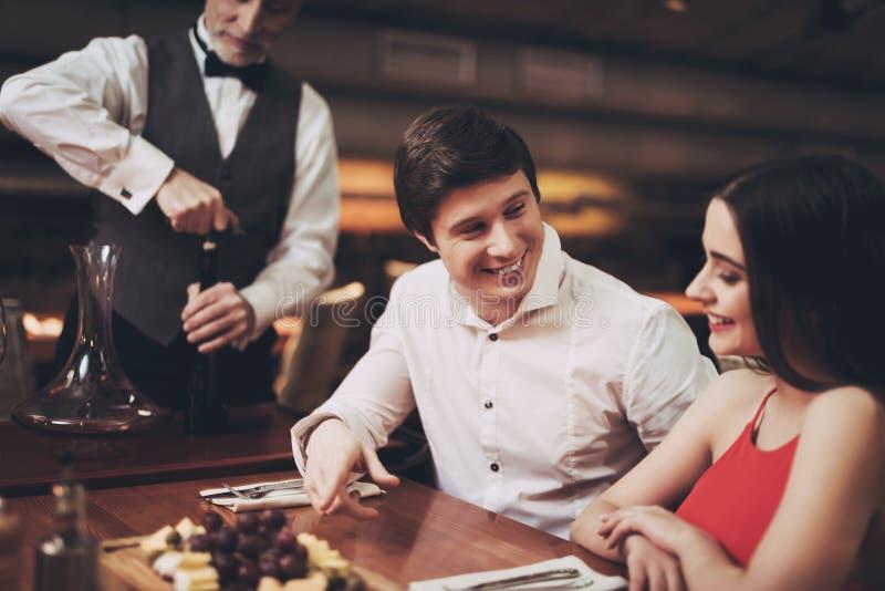 förbunden honom förföra le barn för restaurangen Stilig man och kvinna på datum i restaurang fotografering för bildbyråer