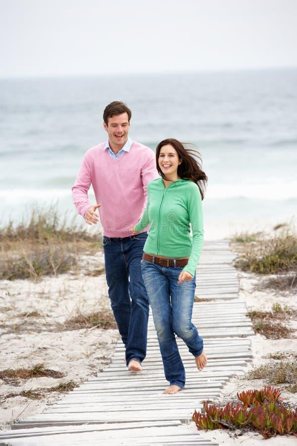 Förbunden running tillsammans längs strandbanan arkivfoto