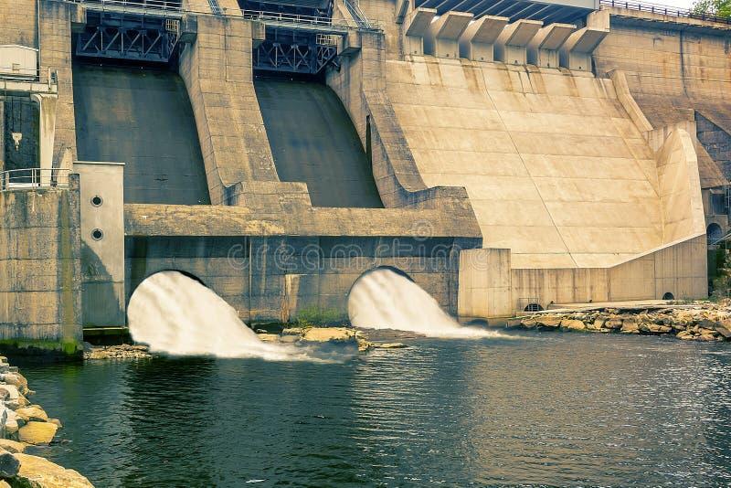 Fördämning och turbiner av en vattenkraftstation med fallande vattenflöden arkivfoto