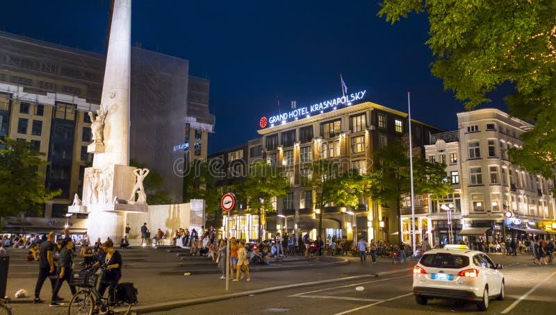 Fördämningfyrkanten i Amsterdam med det Krasnapolsky hotellet - AMSTERDAM - NEDERLÄNDERNA - JULI 20, 2017 royaltyfri fotografi