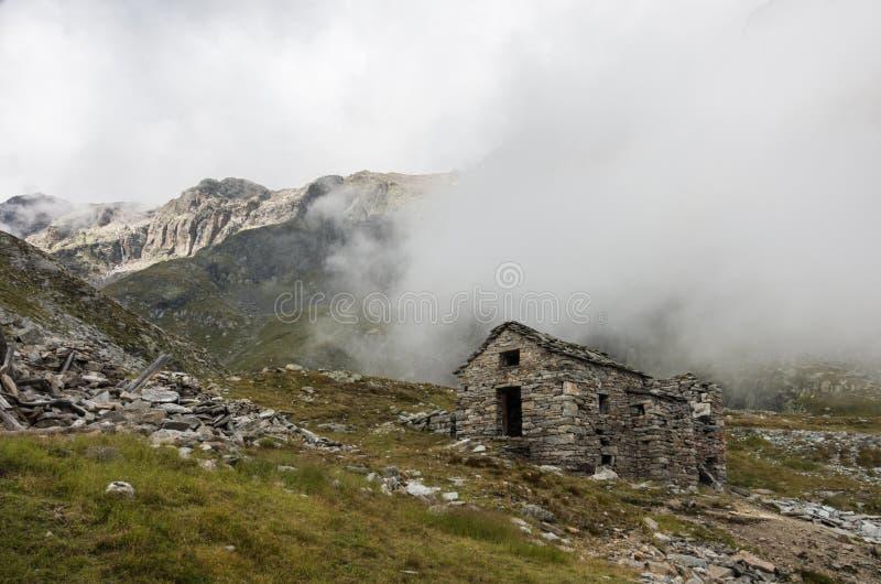 Fördärva av gammal fristad i moln Monte Rosa massiv nära Punta Indren Alagna Valsesia område, royaltyfri bild