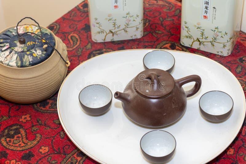 Fördelade den kinesiska teservisen för brun lera ut på en vit platta bredvid traditionell örtte i lerakrukor och tenn på burk arkivbild