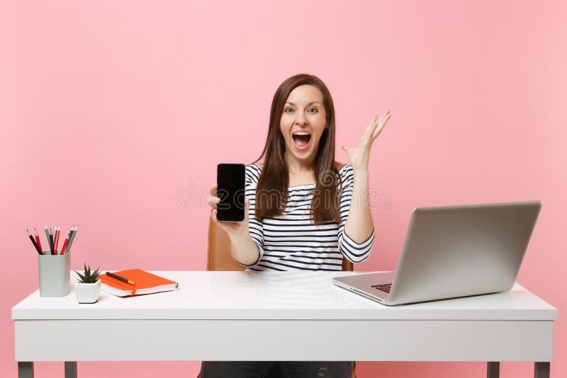 Fördelande händer för extatisk kvinna som rymmer mobiltelefonen med tomt tomt skärmarbete på det vita skrivbordet med modern PC arkivfoton