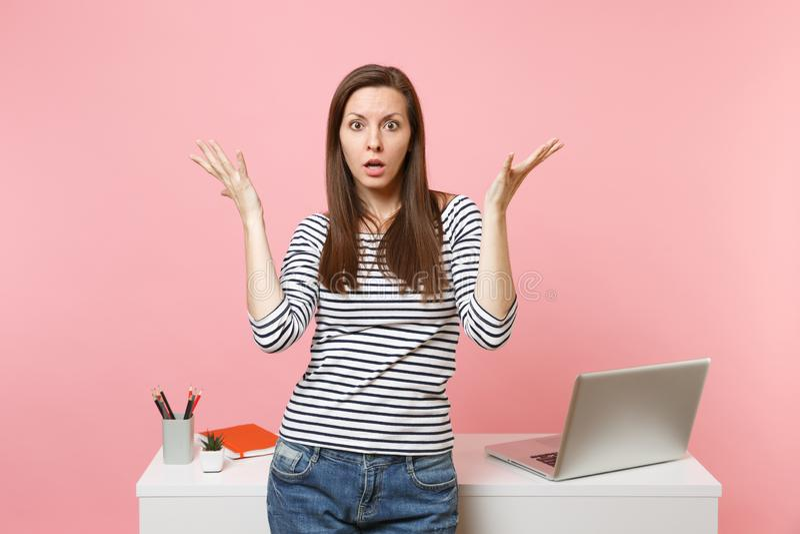 Fördelande handarbete och anseende för ung chockad förvirrad kvinna nära det vita skrivbordet med PCbärbara datorn som isoleras p arkivbilder